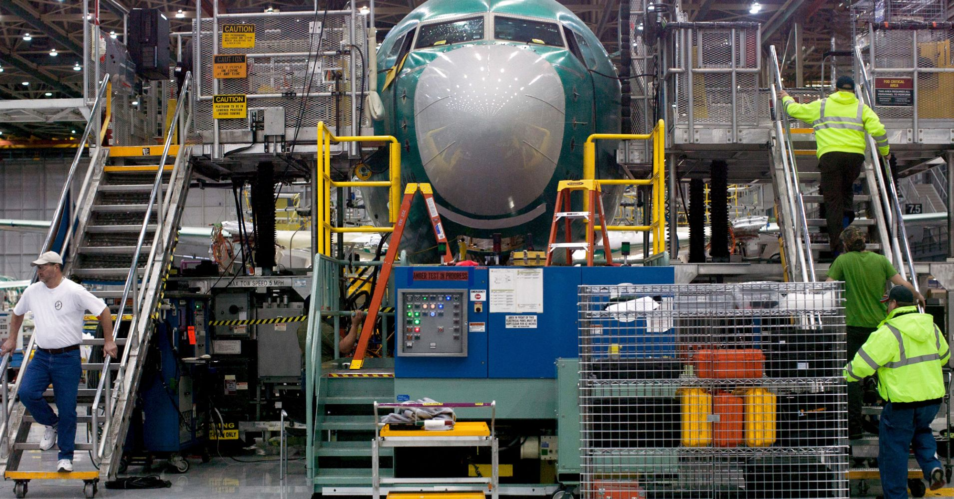 Boeing employees going up and down stairs entering and exiting the Boeing 737 MAX during a media tour at the Boeing plant in Renton, Washington.