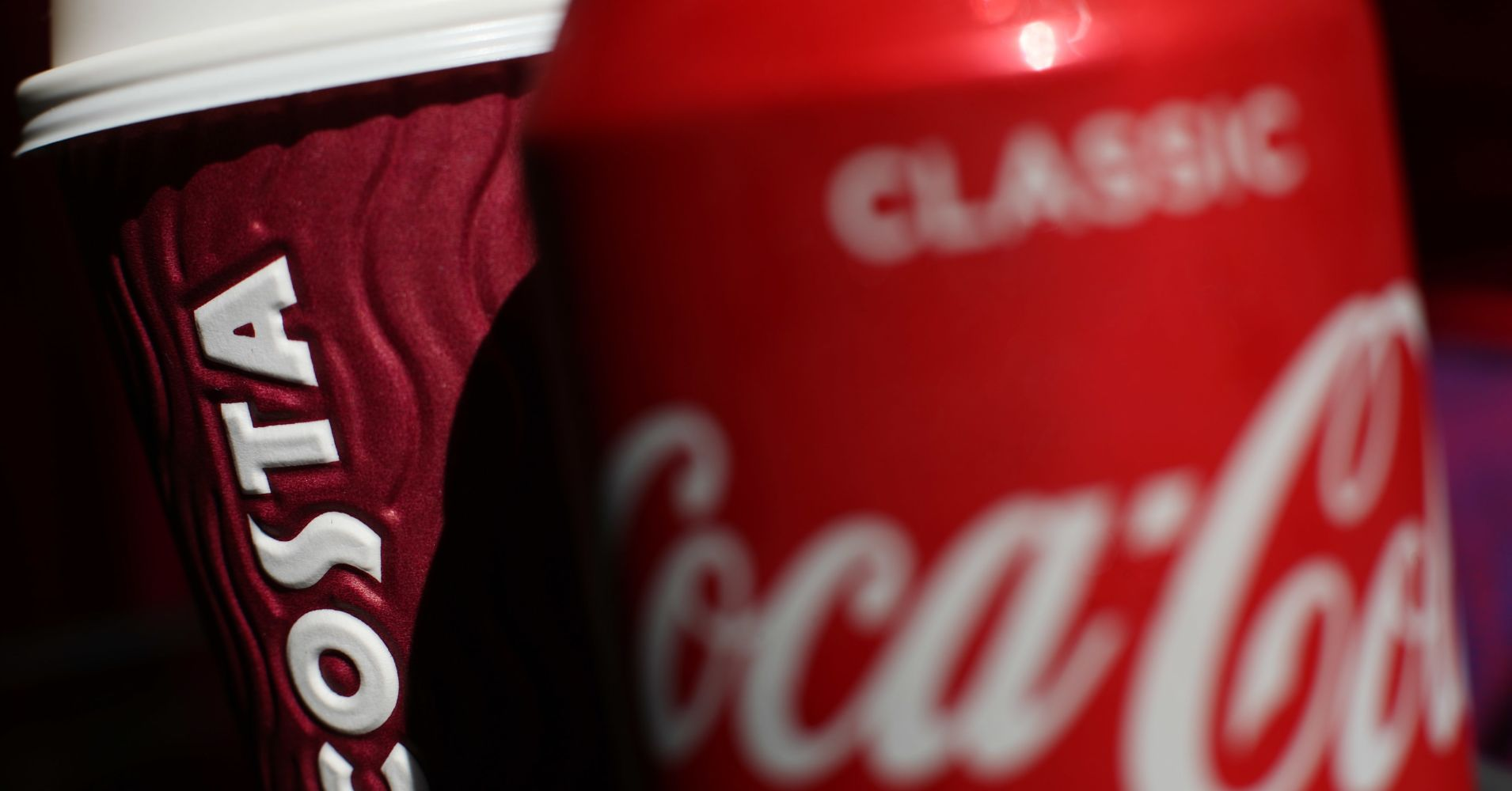A can of Coca-Cola next to a cup of Costa coffee.