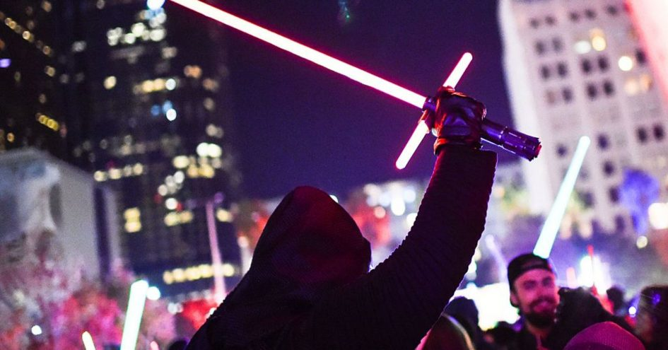 A Star Wars fan dressed as Kylo Ren raises his lightsaber