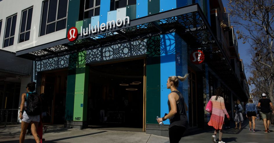 A woman jogs past a Lululemon retail store.