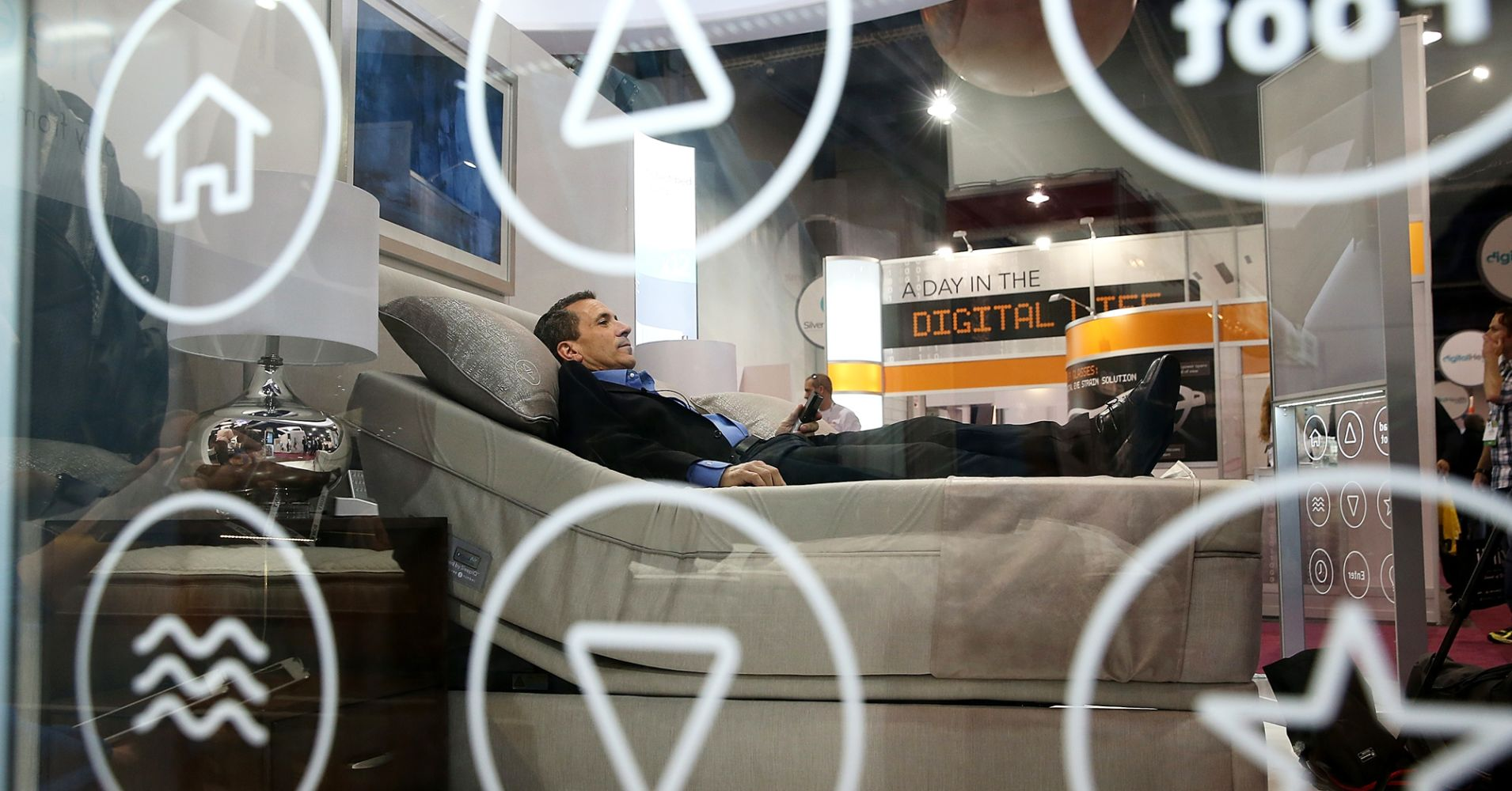 A Sleep Number representative lays on a new Sleep Number bed at the International CES in Las Vegas.