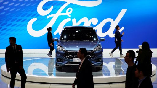 People walk by a Ford Escape SUV displayed during the media day for the Shanghai auto show in Shanghai, China, April 16, 2019.